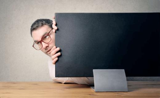 Mand stikker hovedet frem fra en pc-skærms venstre side