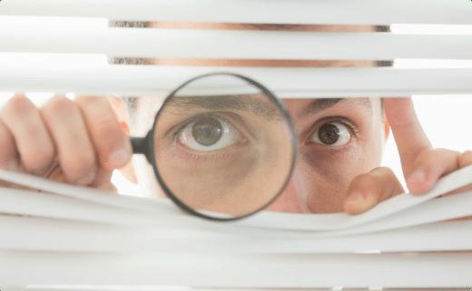 Mand der kigger igennem plasticlamelgardin med forstørrelsesglas